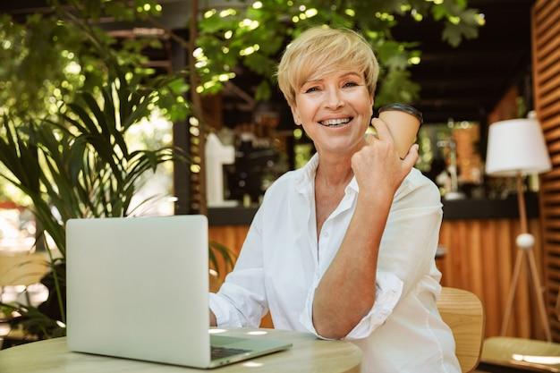 Feliz mulher madura, sentado em um café com o computador portátil