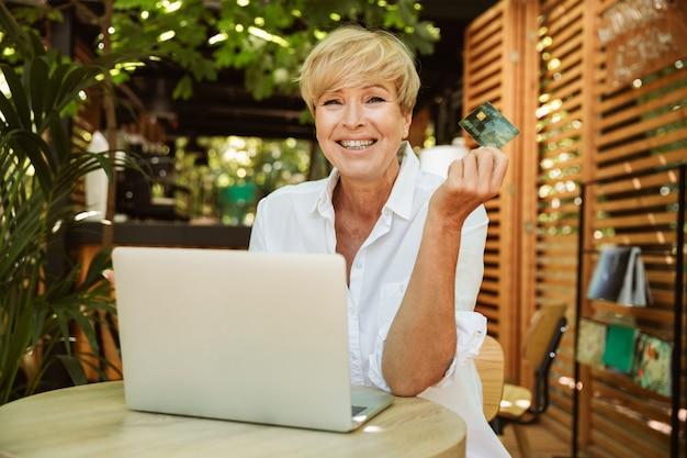 Feliz mulher madura, sentado em um café