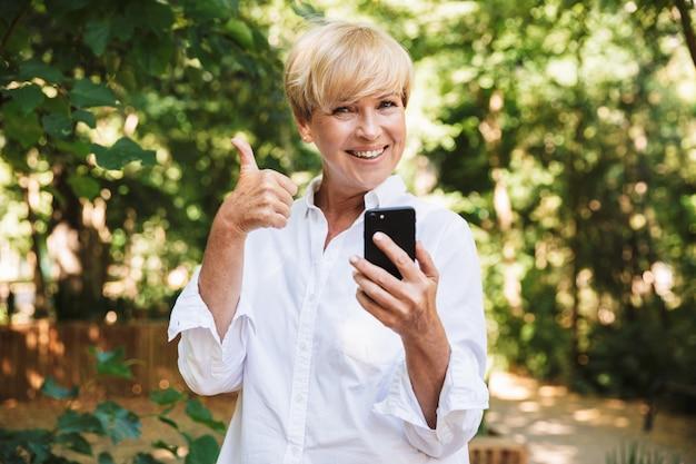 Feliz mulher madura usando telefone celular