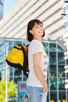 Feliz mulher mais velha, carregando mochila na cidade