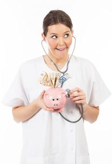 Feliz mulher médico com cofrinho cheio de dinheiro