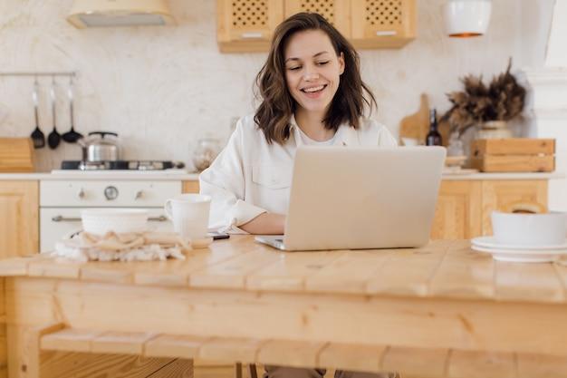 Feliz mulher milenar caucasiana, sentar-se à mesa, trabalhar online no laptop, consultar o cliente na web, sorrindo.