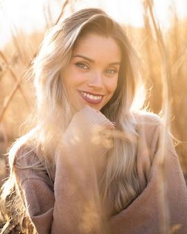 Feliz, mulher moderna, posar, em, luz solar, olhando câmera