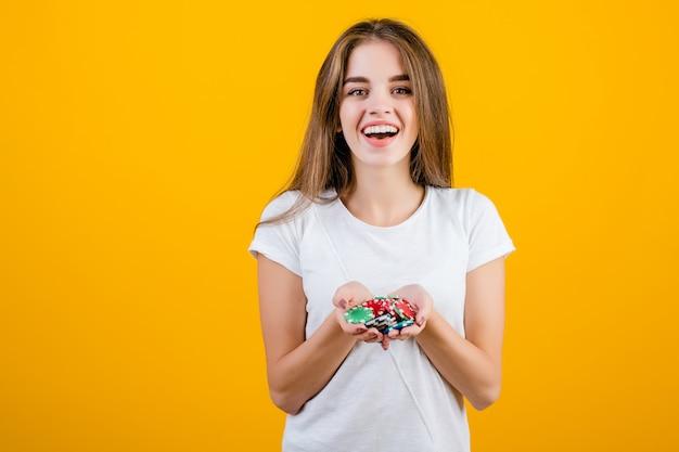 Feliz mulher morena animada feliz com um punhado de fichas de pôquer do casino online isolado sobre o amarelo