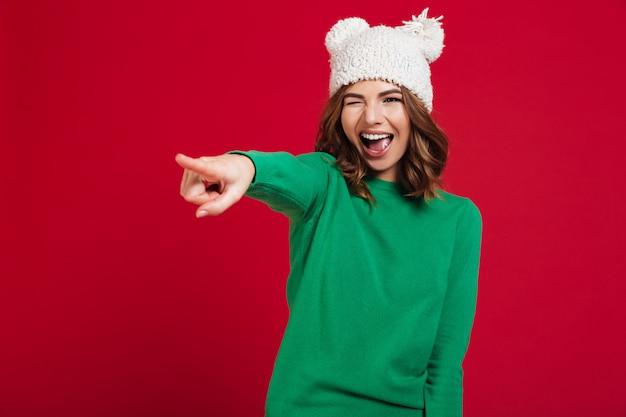 Feliz mulher morena de suéter e chapéu engraçado apontando para fora
