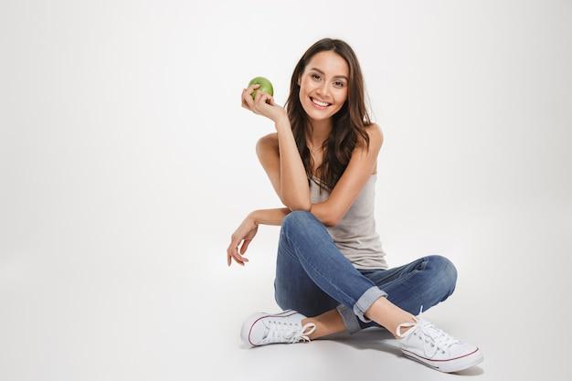 Feliz mulher morena sentada no chão com a apple e olhando para a câmera sobre cinza