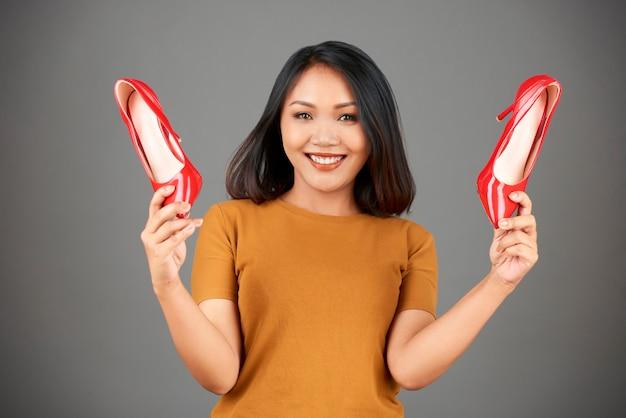 Feliz mulher mostrando salto vermelho