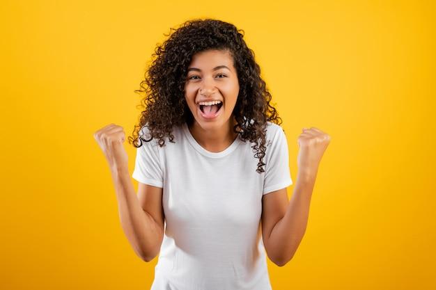 Feliz mulher negra africana mostrando sua vitória isolada sobre amarelo