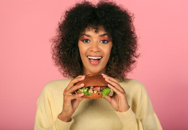 Feliz mulher negra com cabelos ondulados, comendo saboroso cheeseburguer em rosa.