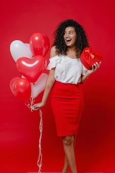 Feliz mulher negra com caixa de presente em forma de coração e balões coloridos isolados na parede vermelha