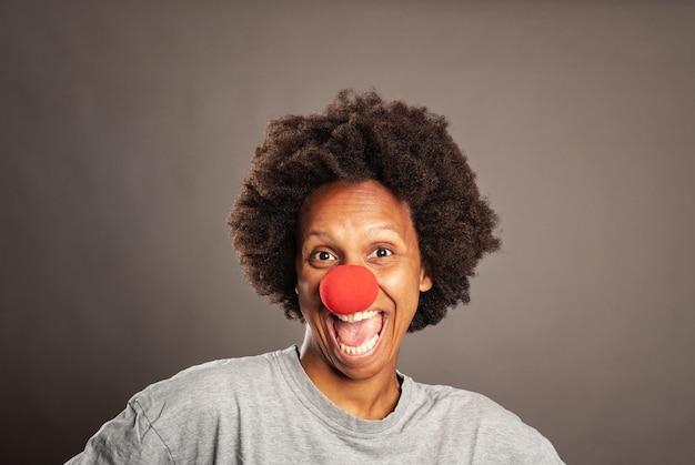 Feliz mulher negra com nariz de palhaço