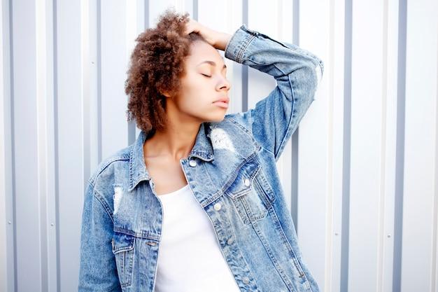 Feliz mulher negra negra afro em jeans e camiseta branca