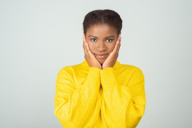 Feliz mulher negra positiva na camisola amarela