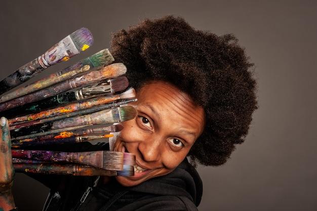 Feliz mulher negra segurando pincéis