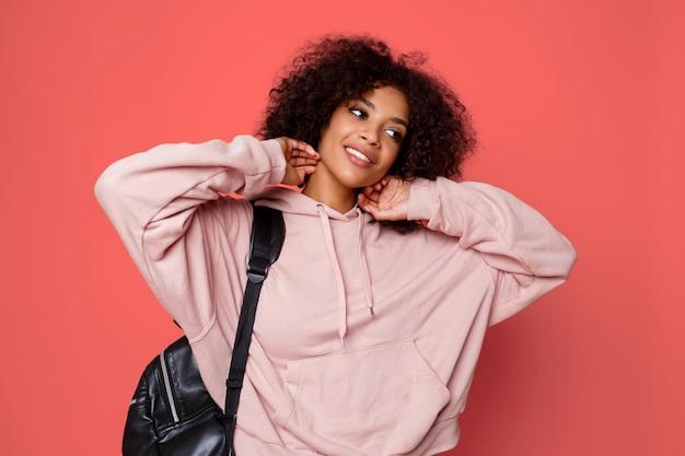 Feliz mulher negra sexy com capuz elegante com mochila posando em fundo rosa e brincando com cabelos encaracolados.