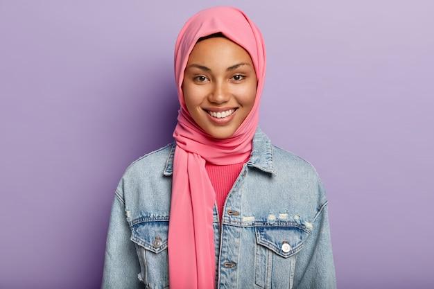 Feliz mulher oriental tem religião islâmica, cabeça coberta com véu rosa, sorri suavemente, mostra dentes brancos, isolada contra parede violeta expressa sentimentos e emoções positivas. etnia