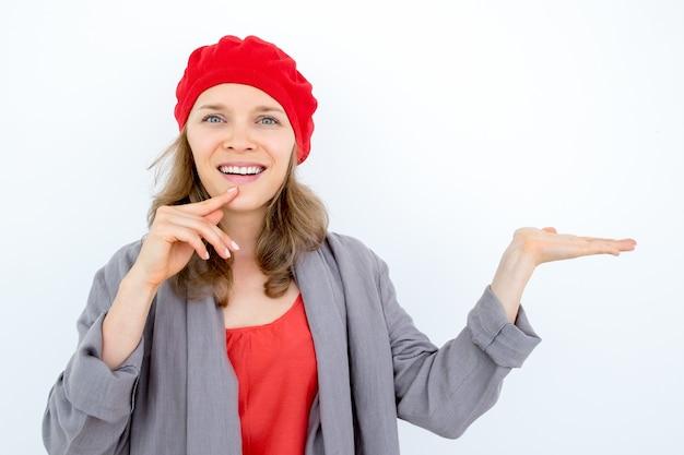 Feliz mulher pensativa que demonstra um bom produto