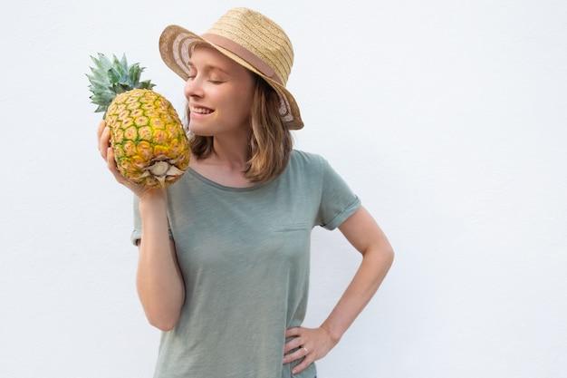 Feliz mulher positiva no chapéu de verão cheirando abacaxi inteiro