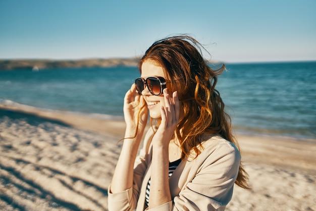 Feliz mulher ruiva com jaqueta bege e camiseta na areia perto do mar nas montanhas