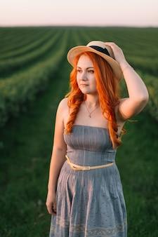 Feliz mulher ruiva com um chapéu em um campo verde