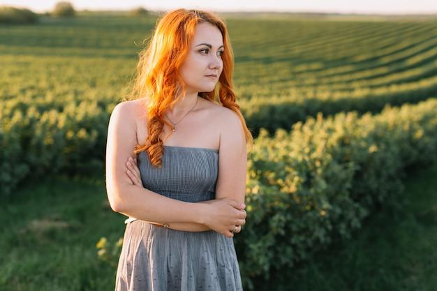 Feliz mulher ruiva em um campo verde