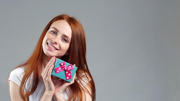Feliz mulher ruiva satisfeita, segurando uma caixa de presente nas mãos dela