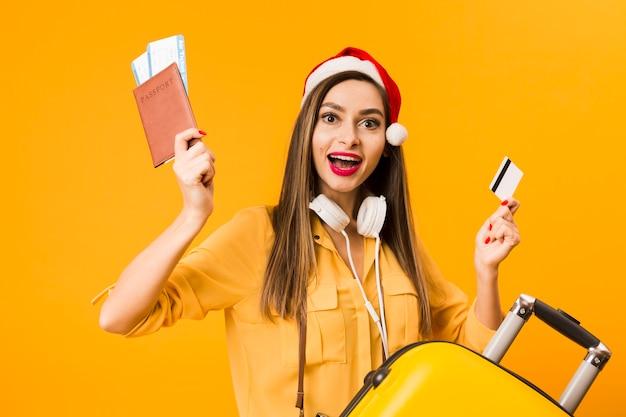Feliz mulher segurando bilhetes de avião e cartão de crédito posando ao lado de bagagem
