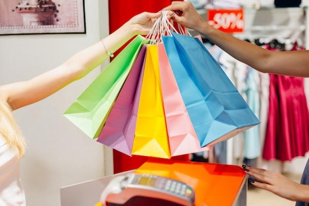 Feliz mulher segurando compras muitos saco de cores