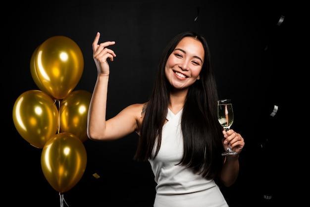 Feliz mulher segurando copo de champanhe na festa de ano novo