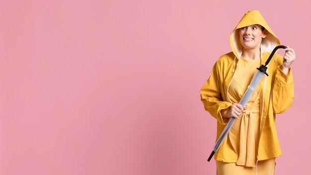 Feliz mulher segurando um guarda-chuva com espaço de cópia