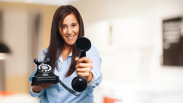 Feliz mulher segurando um telefone com seletor giratório