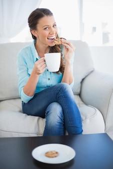 Feliz mulher segurando xícara de café comendo biscoito