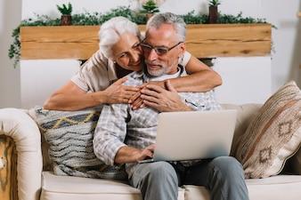 Feliz, mulher sênior, abraçar, dela, marido, detrás, sentar sofá, com, laptop