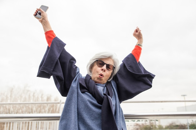 Feliz mulher sênior, levantando os braços e gritando ao ar livre