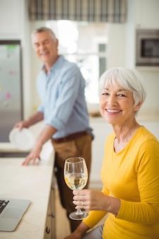 Feliz mulher sênior segurando copo de vinho na cozinha