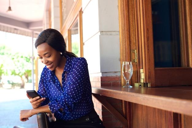 Feliz, mulher senta-se barra, sorrindo, com, telefone móvel