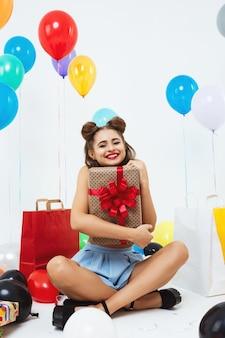 Feliz mulher senta-se em posição de lótus, segurando a caixa de presente grande