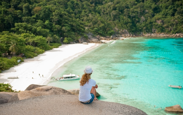 Feliz mulher sentada em uma pedra grande na praia tropical em camisa branca e chapéu de vime