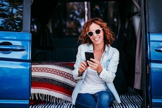 Feliz mulher sentada em uma van azul e se divertindo. conceito de viagens. mulher usando telefone celular