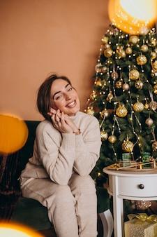 Feliz mulher sentada no sofá junto à árvore de natal