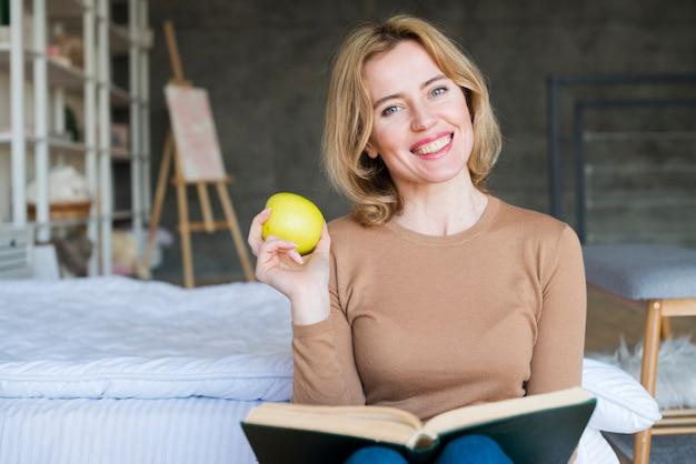 Feliz, mulher, sentando, com, livro, e, maçã
