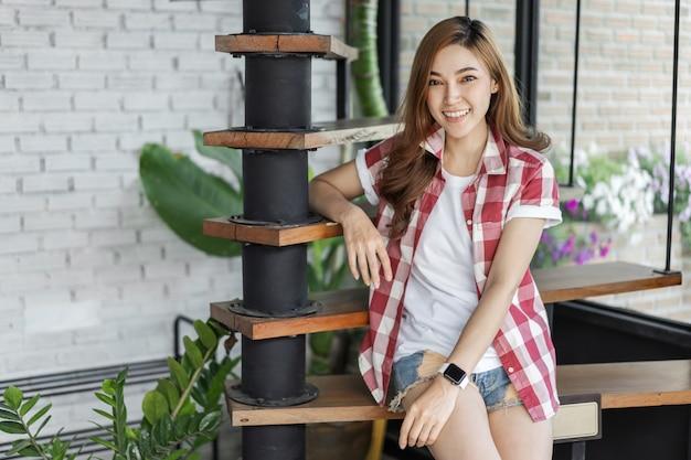 Feliz, mulher, sentando, ligado, madeira, escada