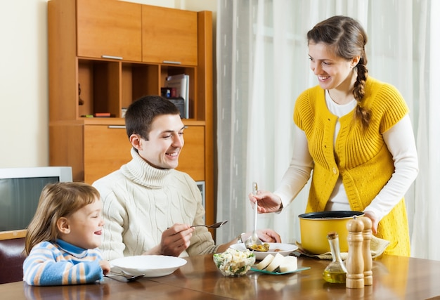 Feliz mulher servindo sopa para família