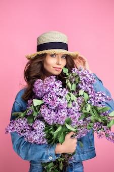 Feliz mulher sorridente no chapéu de palha posando com buquê de flores lilás