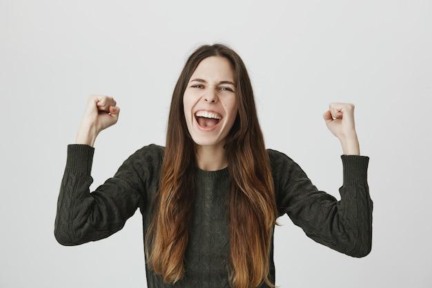 Feliz mulher sorridente, regozijando-se, expressar excitação, punho bomba cantando