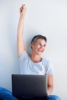 Feliz, mulher velha, usando computador portátil, com, mão levantada, abasing, branca, parede
