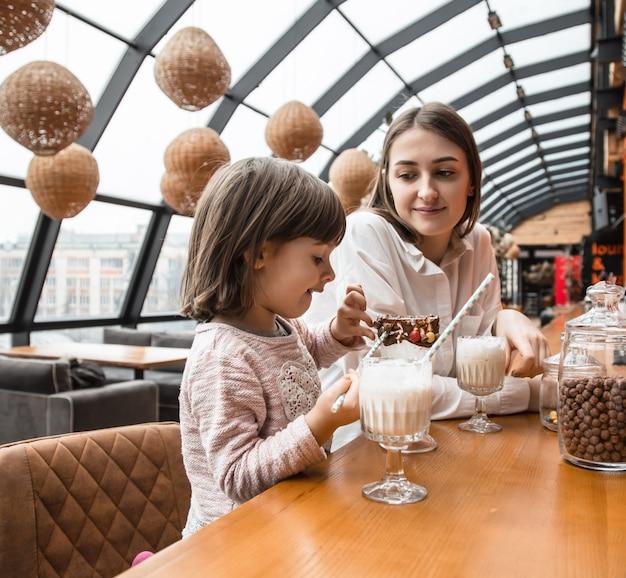 Feliz mulheres jovens mãe com crianças bebendo um milk-shake