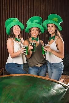 Feliz mulheres jovens segurando copos de bebida perto da mesa
