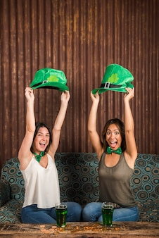 Feliz, mulheres jovens, segurando, são, patricks, chapéus, perto, tabela, com, copos, de, bebida