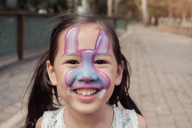 Feliz, multicultural, asain, menina, com, coelhinho coelho, pintura cara